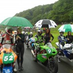 Grid girls on start line with umbrella raining