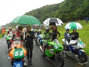 Grid girls on start line with umbrella raining